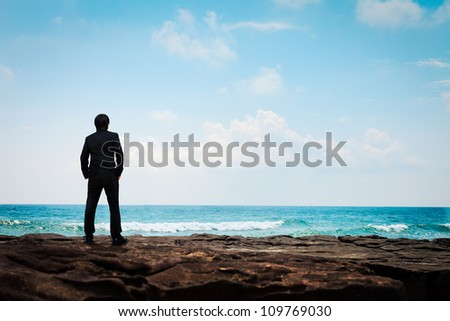Portrait young business man in suit face to the sea, Film tone - stock photo