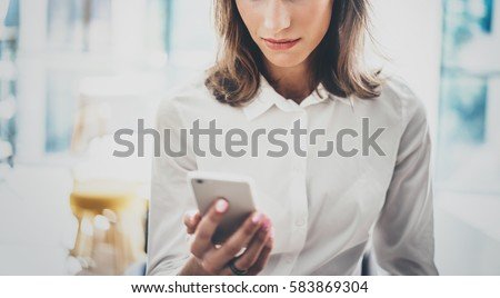Portrait young business woman wearing white shirt using modern smartphone hands.Girl reading sms message in working process at sunny office.Panoramic windows background.Horizontal blurred