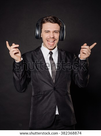 portrait young businessman in black suit singing with loud music in the ears. emotions, facial expressions, feelings, body language, signs. image on a black studio background. - stock photo