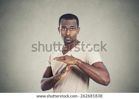 Portrait young confident casual man showing time out gesture with hands isolated grey wall background. Human emotion face expression body language sign symbol - stock photo