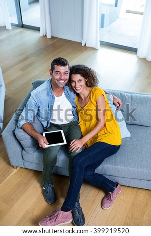 Portrait young couple sitting on sofa and using digital tablet in living room - stock photo