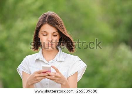 portrait young dark-haired pretty girl park holds mobile phone and reads message, background summer green park - stock photo