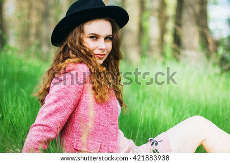 Portrait young elegant woman in pink coat and black hat. Fashion outdoors shot, street style concept. Blogger outfiit. Photo toned  vsco filters. Spring portrait of stylish model, posing in the park