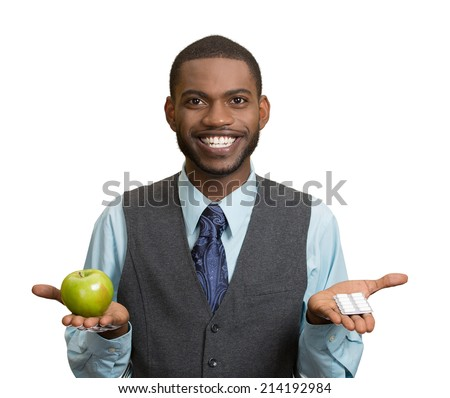 Portrait young, fit, happy handsome man holding green fresh apple in one hand, pills, vitamins in another. Sugar free chewing gum, dentist recommended. Face expressions, emotion, health care. Dieting - stock photo