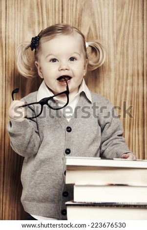 Portrait young girl in glasses next to books - stock photo
