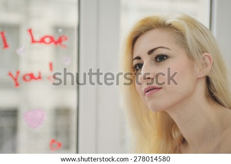 "Portrait  young girl with inscription at a window ""I love you!"""