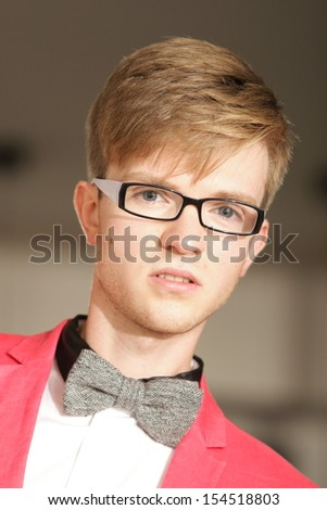 Portrait young handsome stylish man fashion model in glasses wearning bright red jacket and bow tie posing indoor