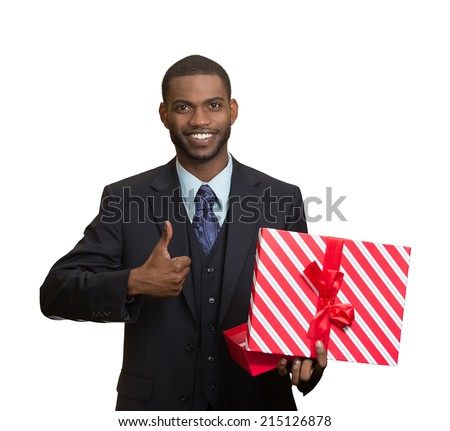 Portrait young happy, smiling business man holding present, red gift box, giving thumb up isolated white background. Positive facial expressions, human emotion body language, life perception, attitude - stock photo