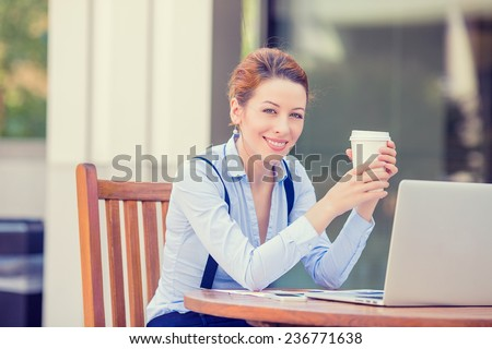 Portrait young happy woman drinking holding coffee cup working on computer laptop outside corporate office isolated city background, college campus. Positive human face expression, emotion, success