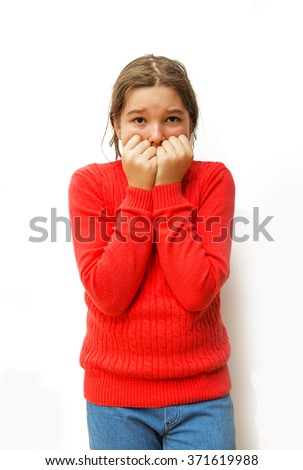 Portrait young little girl biting her finger nails, looking at you with fear of something, anxious isolated  - stock photo
