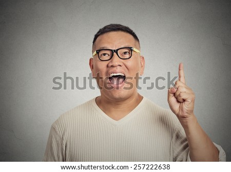 Portrait young man has an idea, pointing with finger up isolated on grey wall background. Excited guy with solution for a problem. Human face expression body language, life perception creativity - stock photo