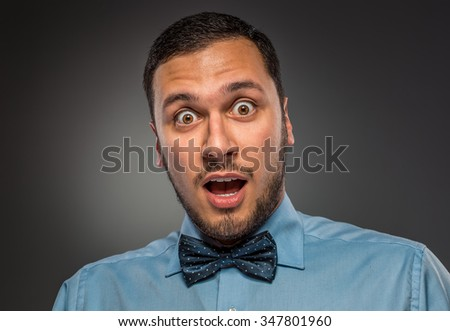 Portrait young man in blue shirt and butterfly tie looking at the camera with amazement, isolated on gray studio background. Human emotion, facial expression. Closeup - stock photo