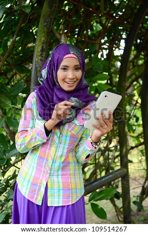 Portrait young muslim women relaxed at the park with smart phone