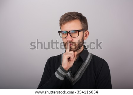 portrait young serious man in glasses placing finger on lips saying, shhh, be quiet - stock photo