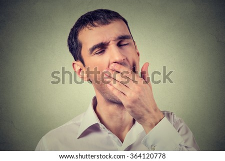 Portrait young sleepy man yawning isolated on gray wall background. Sleep deprivation, burnout, laziness concept - stock photo