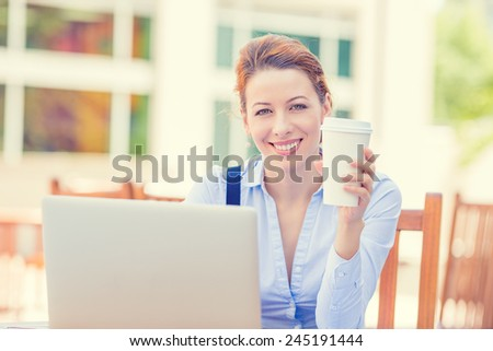 Portrait young smiling woman working on laptop outside corporate office drinking coffee isolated city building background college campus. Positive human face expression, emotion, life success concept - stock photo