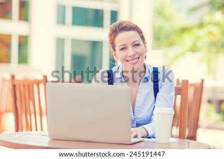 Portrait young smiling woman working on laptop outside corporate office drinking coffee isolated city building background college campus. Positive human face expression, emotion, life success concept