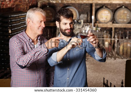 Portrait young sommelier standing at family wine cellar with senior winemaker and tasting a glass of red wine. Small business.  - stock photo