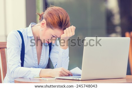 Portrait young stressed displeased worried business woman sitting in front of laptop computer isolated outdoors city building background. Negative face expression emotion feelings problem perception