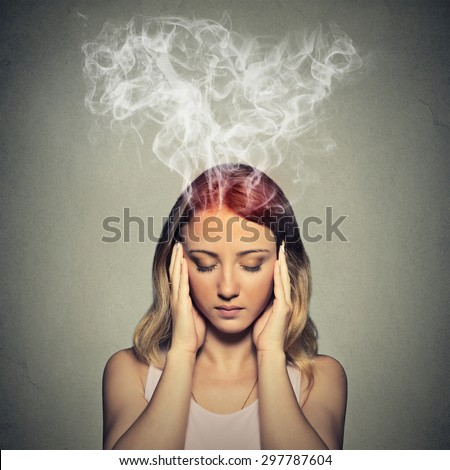 Portrait young stressed woman thinking too hard steam coming out up of head isolated on grey wall background. Face expression emotion perception - stock photo