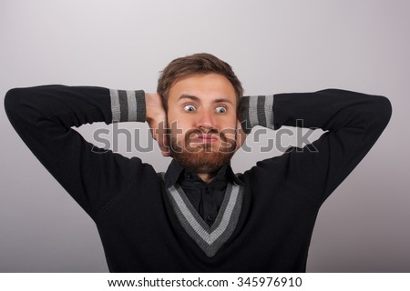 Portrait young surprised man holding head with hands. Human face expression emotion - stock photo