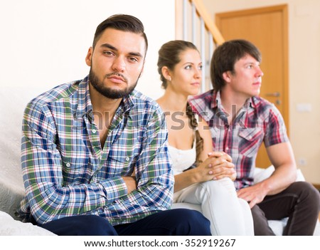 portrait young unhappy man in polygamous family indoors