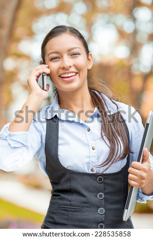 Portrait young woman, attractive businesswoman talking on cell phone having pleasant conversation receiving good news walking in park isolated outdoors autumn tree background. Positive face expression - stock photo