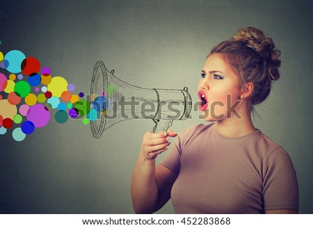 Portrait young woman holding screaming in megaphone isolated on gray wall background. Negative face expression emotion feelings. Propaganda, breaking news, power, social media communication concept - stock photo