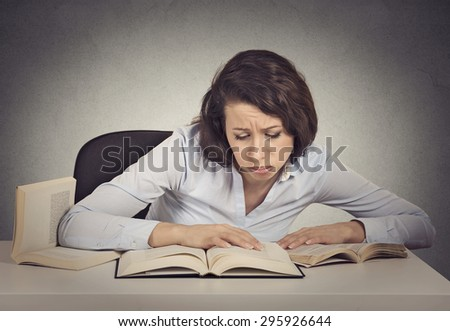 Portrait young woman student with desperate expression looking at her books, too much work to do  - stock photo