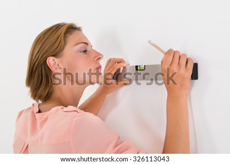 Portrait Young Woman Taking Measurements Of The Wall With Spirit Level