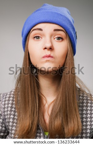 Portrait young woman with angry expression on a gray - stock photo