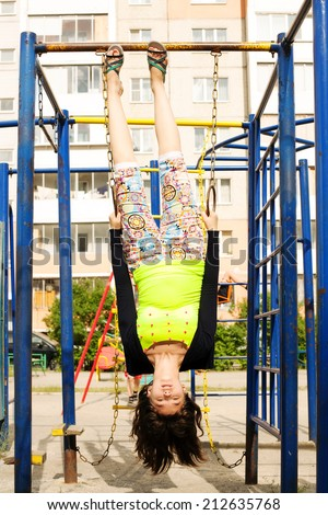 Portraits of happy girl playing upside down  on playground   - stock photo
