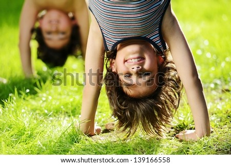 Portraits of happy kids playing upside down outdoors in summer park - stock photo