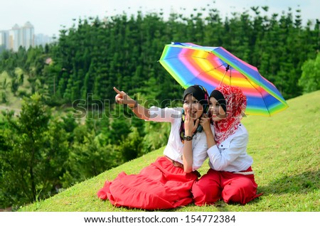 Portraits of two young muslim woman holding umbrella - stock photo