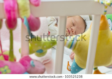 Portraot of sleeping newborn baby,view through the fence at the crib. - stock photo