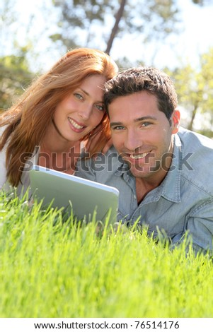 Portrat of couple laying down the grass with touchpad