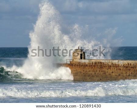 Portreath pier big white water wave splash, Cornwall UK. - stock photo