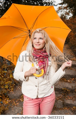 Portret of a lovely sunny beautifull girl standing under the autumn umbrella in the park