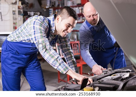 Portret to professional mechanics repairing car of client - stock photo