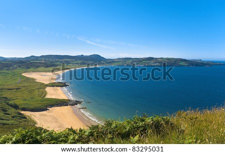 Portsalon, Donegal, Ireland, where the golden sands of a deserted beach and the deep blue waters of Lough Swilly, an inlet of the Atlantic Ocean, bask in the sunshine on a hot summer day.