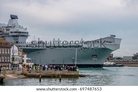 Portsmouth, Hampshire, England. 16th August 2017. The Royal Navy;s latest aircraft carrier HMS Queen Elizabeth enters her new home port of Portsmouth Harbour fot the first time