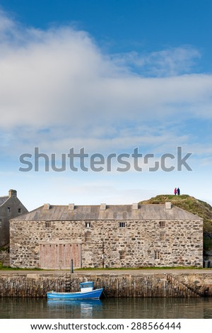 Portsoy harbour with small blue boat and old stone store building. - stock photo