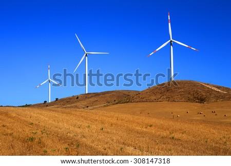 Portugal, Alentejo Region, Wind power turbines in an autumn crop field against a deep blue sky - stock photo
