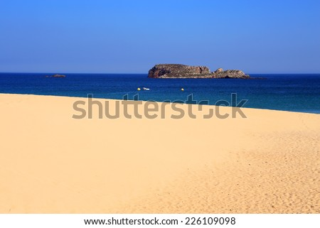 Portugal, Algarve, Sagres, beautiful turquoise Atlantic Ocean with crystal clear water washing onto a deserted Martinhal Beach with powdery sand. Clear horizon. Blue sky. - stock photo