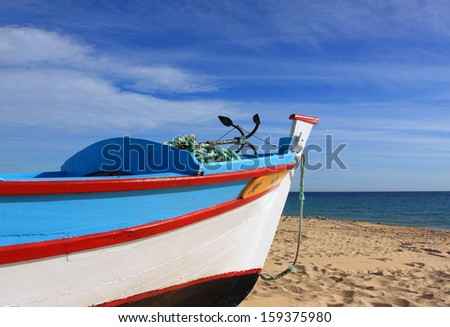 Portugal, Algarve, typical colourful wooden fishing boat on the beach.