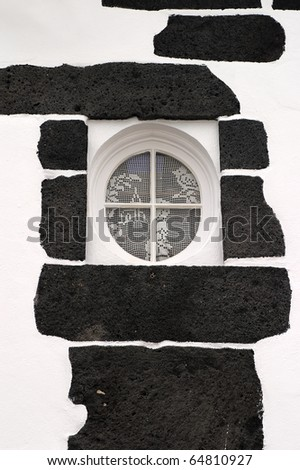 Portugal Azores Islands Sao Miguel typical round window built into black volcanic rock - stock photo
