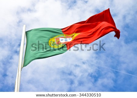 Portugal flag view from below waving against a blue sky, motion blur
