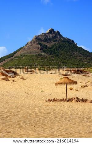 Portugal, Madeira, Porto Santo, deserted beach, straw parasol and rocky peak in background. - stock photo