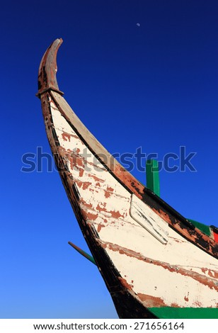 Portugal, Setubal District, Almada,  Caparica Coast. Bow of a disused typical coastal fishing boat against a deep blue sky in the late afternoon sunlight. - stock photo