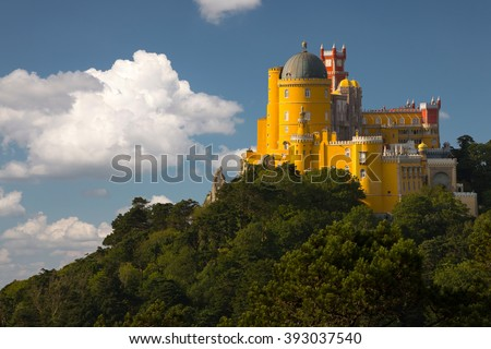 Portugal. Sintra. The Pena Palace on a cliff surrounded by forest and clouds - stock photo